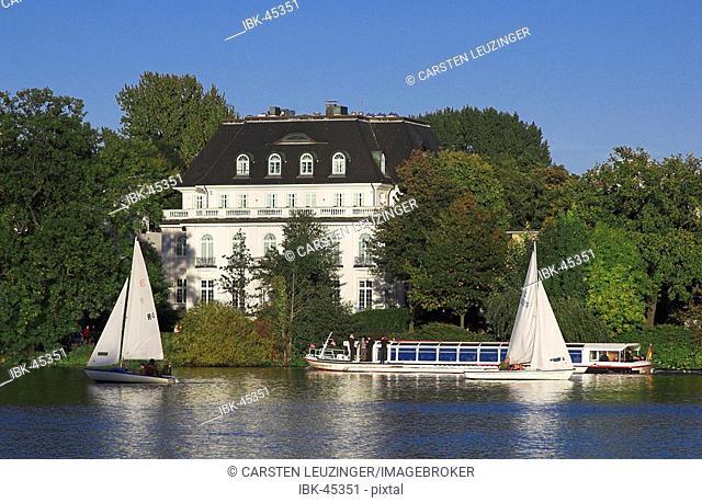 Sail boat in front of a villa at lake Alster in Hamburg, Germany