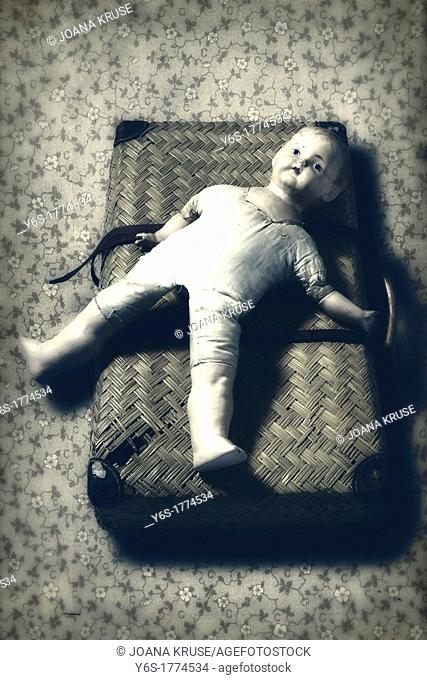 an old, broken doll lies on an old suitcase