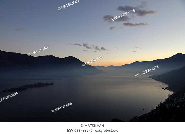 Alpine lake with fog in blue hour with island and mountain