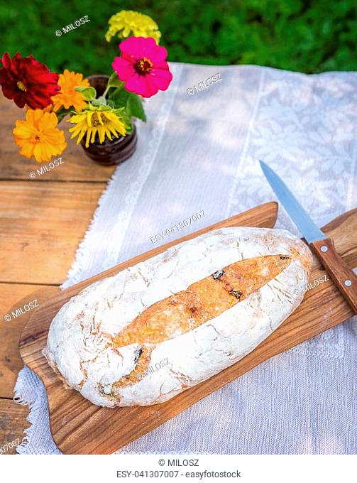 Still life with organic bread. Tasty fresh baked bread photographed on table in garden