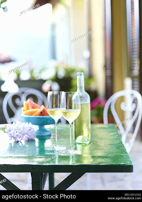 Cold white wine in glasses and a bottle on a green table