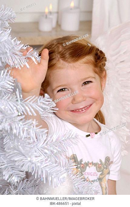 Child decorates a white christmas tree