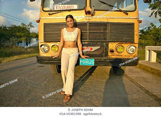 Smiling girl posing in front of an old school bus in the Valle de Viñales, in central Cuba
