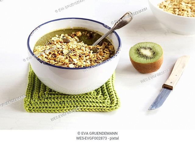 Bowl of green smoothie with mix of oatflakes and granola