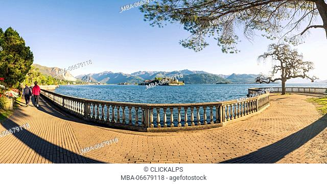 Stresa, Lake Maggiore, Verbano-Cusio-Ossola, Piedmont, Italy. Couple walking on the lake front with Borromean islands in the background