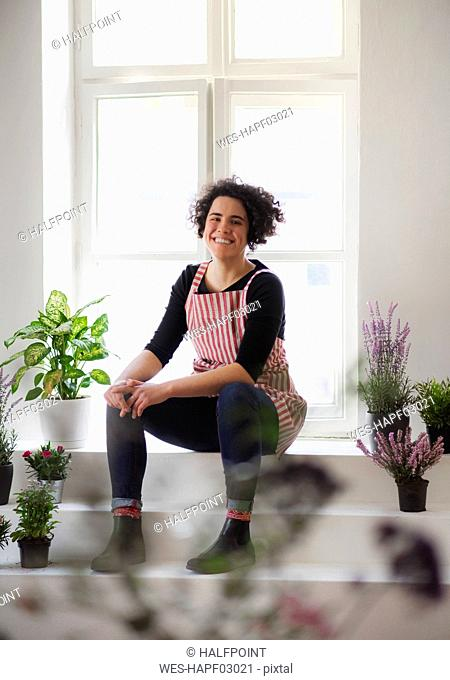 Smiling young woman sitting on stairs in a small shop with plants