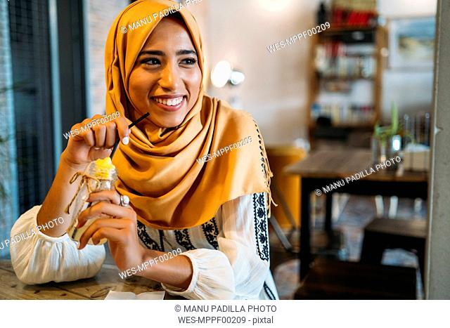 Young muslim woman wearing yellow hijab in a cafe