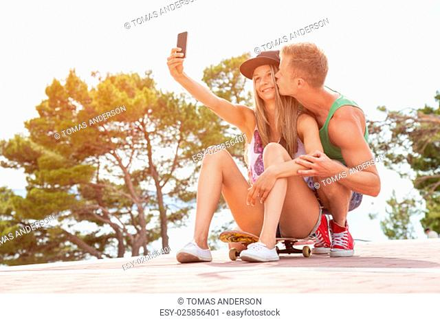 Happy couple with sitting outdoors on skateboard and taking a selfie