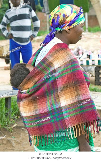 Zulu woman with child on her back dressed in brightly colored clothing, Zululand, South Africa