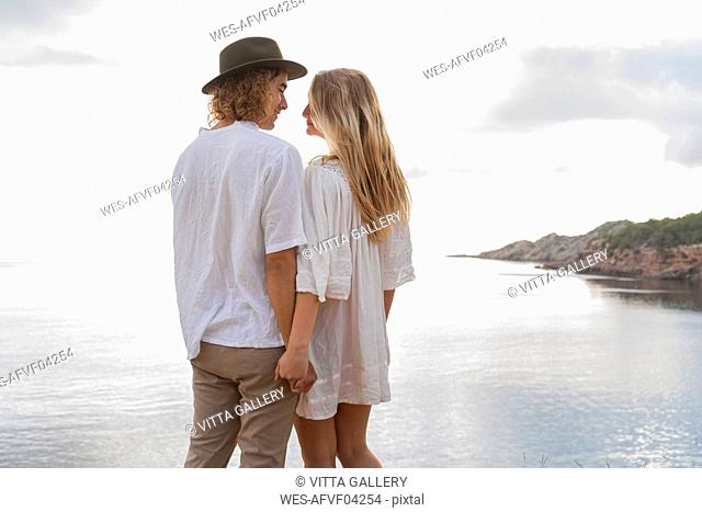 Young couple in love standing in front of the sea holding hands, Ibiza, Balearic Islands, Spain