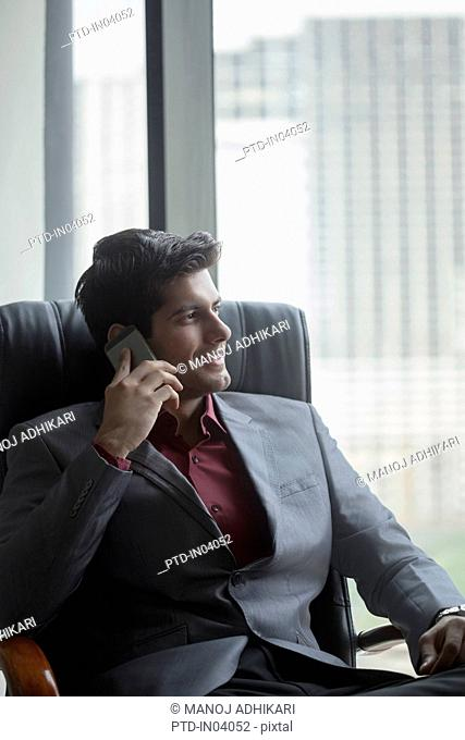 India, Businessman in suit sitting in chair and using mobile phone