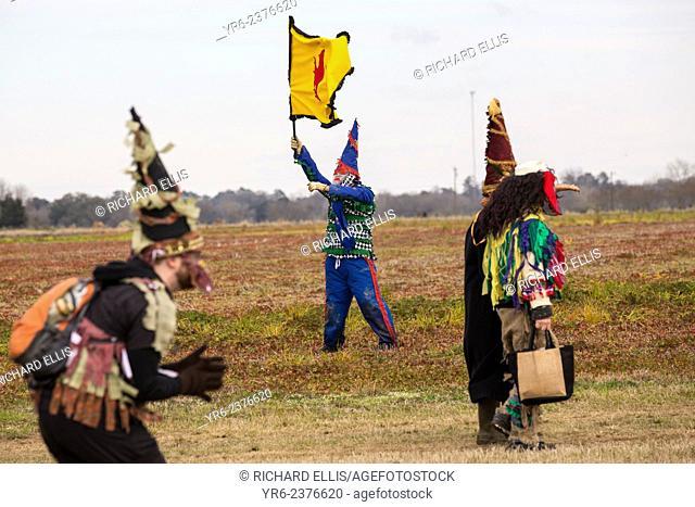 Costumed revelers walk across a farm field during the Faquetigue Courir de Mardi Gras chicken run on Fat Tuesday February 17, 2015 in Eunice, Louisiana