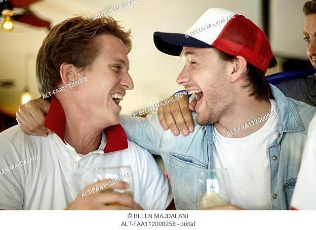 Sports enthusiasts celebrating together in bar