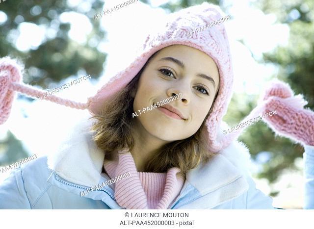 Preteen girl holding strings of knit hat, portrait