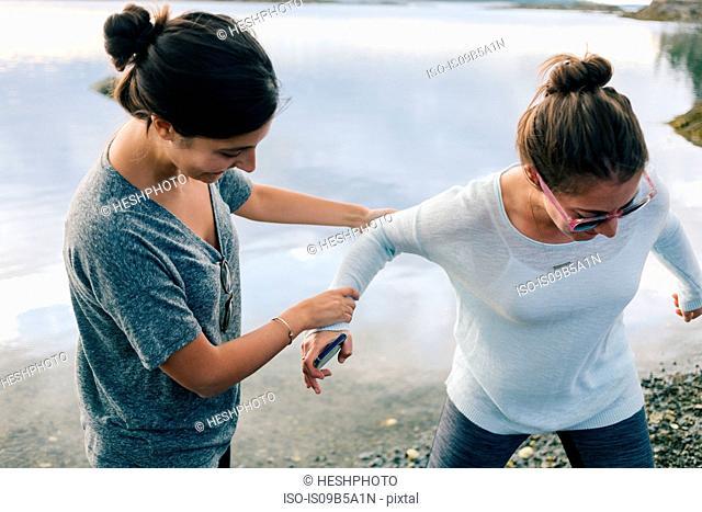 Woman helping sister on shingle beach, Maine, USA