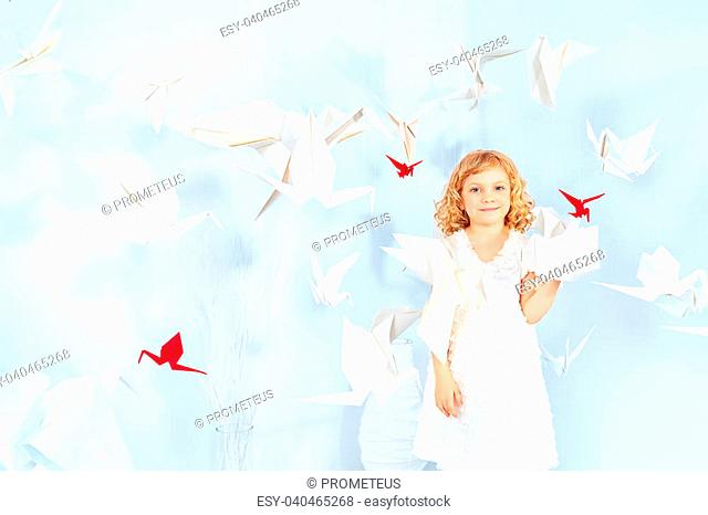 Beautiful little girl in her dream world surrounded with paper birds