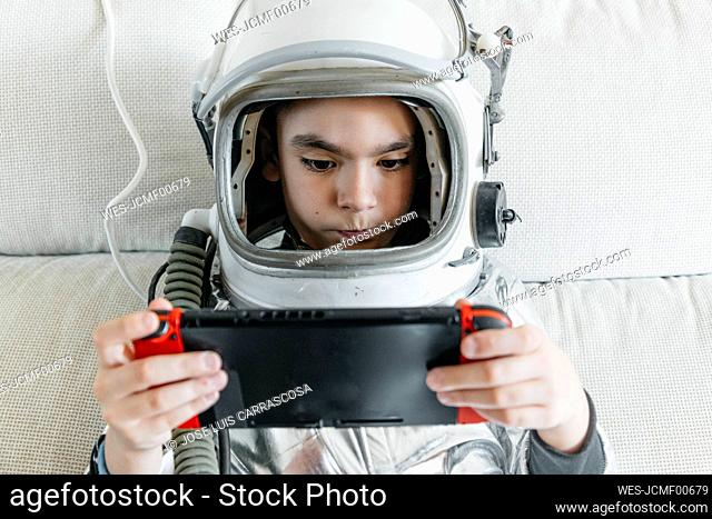 Boy playing video game on a games console, wearing space hat