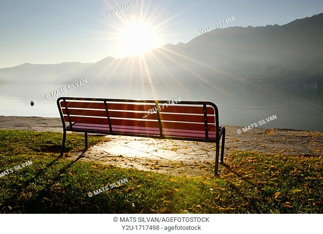 Bench in backlight with sunbeam on a foggy lake front with mountains in ascona ticino