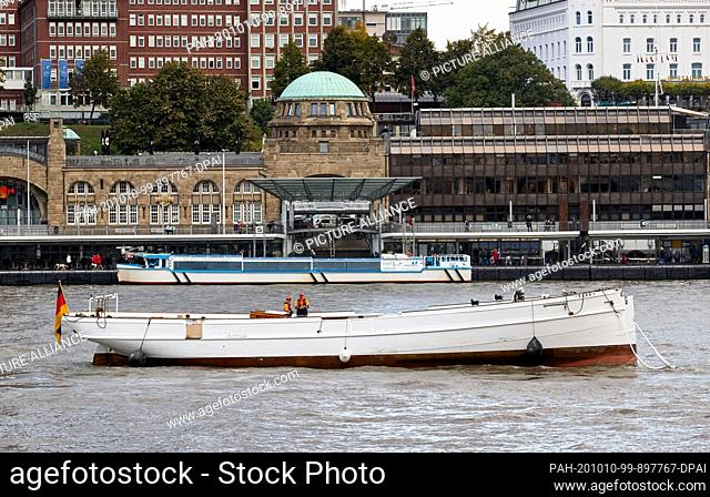 """07 October 2020, Hamburg: Pilot schooner """"""""No. 5 Elbe"""""""" is towed up the Elbe into the Hansa harbour. In the background you can see the landing stages"""