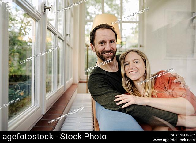 Happy couple sitting on couch, with arns around, smiling
