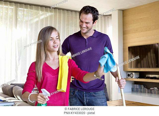 Girl cleaning a glass door beside her father
