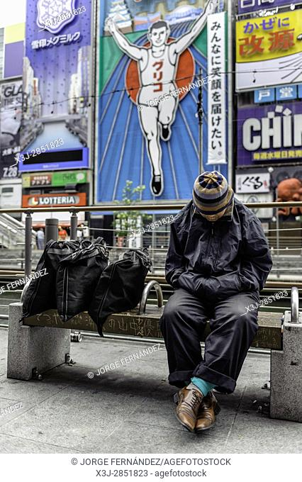 Poor man having a nap sitting on a bench in front of the famous add of the man of Dotombori