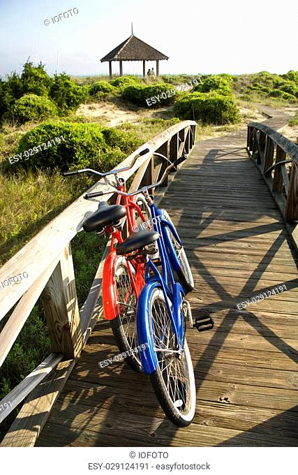 Image of red and blue bike leaning against railing of boardwalk