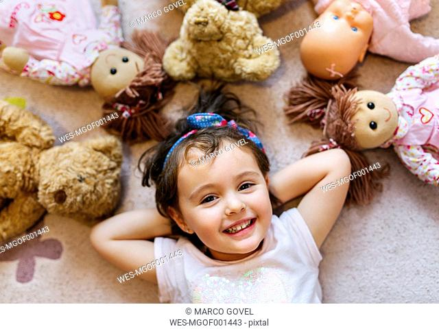 Portrait of smiling little girl lying on the floor with teddies and dolls around her