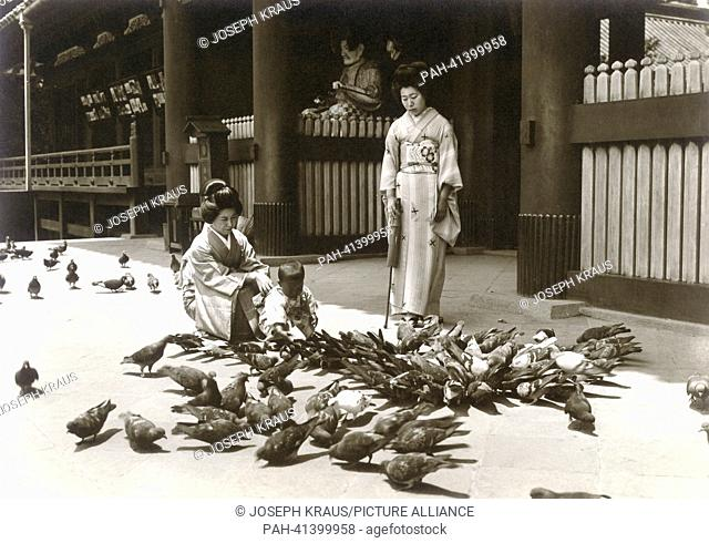 Women feeding doves in front of the gate to the Daibutsu temple. - Kamakura/Japan