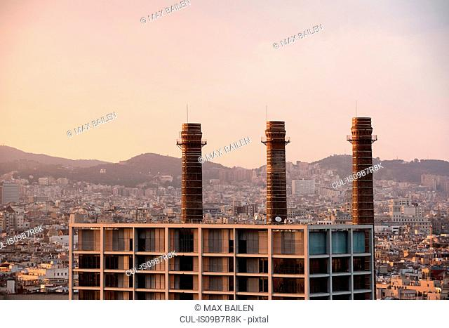Elevated cityscape with row of smoke stacks, Barcelona, Spain