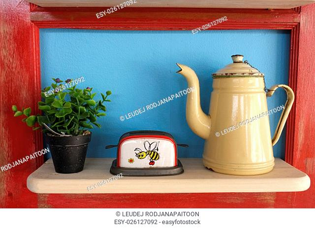 Retro kitchenware and plant pot on wooden shelf, blue background with red frame
