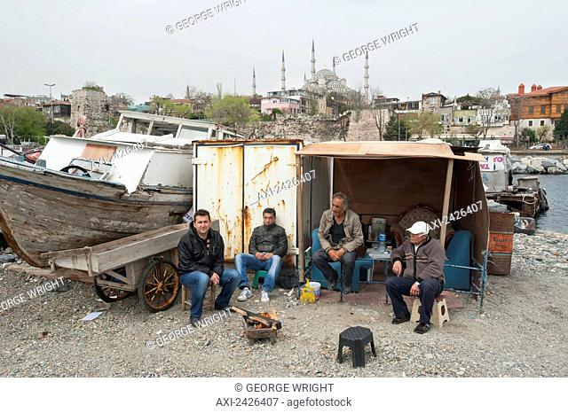 Men sitting outside a shed on the shore beside a boat on a trailer; Istanbul, Turkey