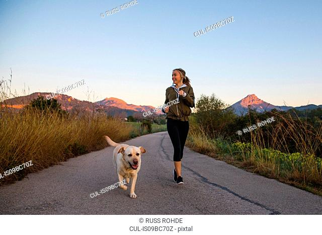 Young woman running along rural road with pet dog