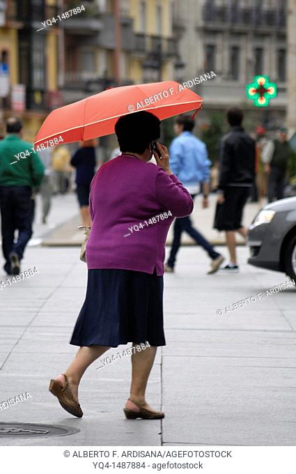 Lady with umbrella on a rainy day in Aviles, Asturias, Spain