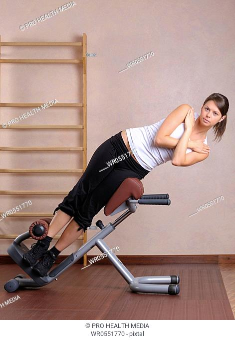 young woman training at a gym machine