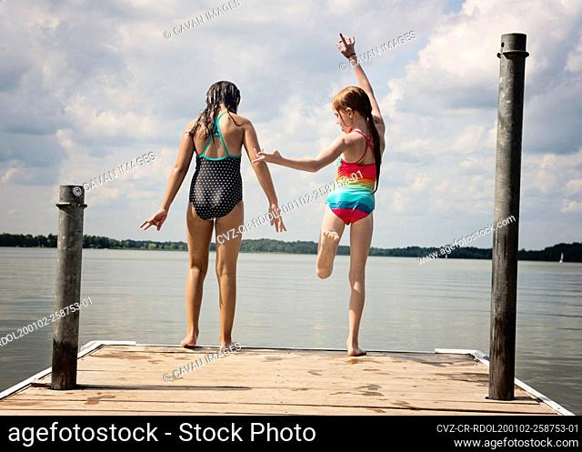 Two Young Girls in Swimsuits About to Jump off a Dock Into a Lake