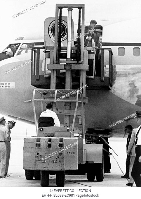 President John F. Kennedy on crutches disembarking from Air Force One by fork lift. Kennedy injured his back planting a ceremonial tree during a state visit to...