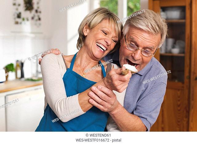 Germany, Kratzeburg, Senior woman feeding senior man