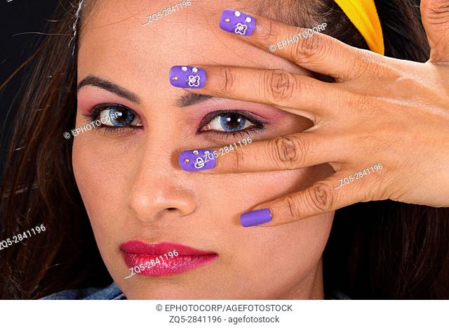 Portrait of young woman with hand with painted nails on face