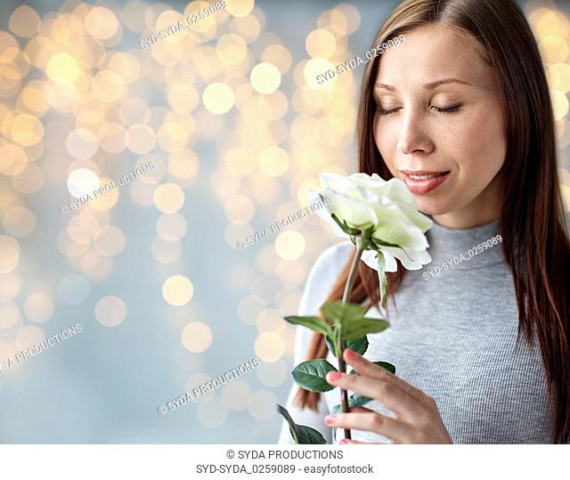 woman smelling white rose over festive lights