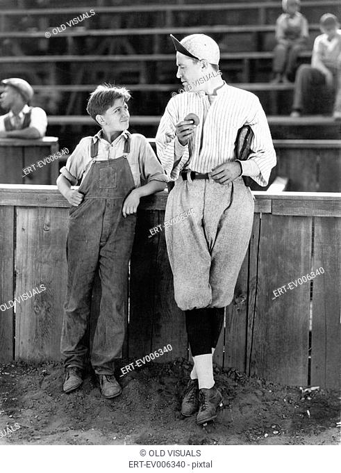Father and son standing together on a baseball field All persons depicted are not longer living and no estate exists Supplier warranties that there will be no...