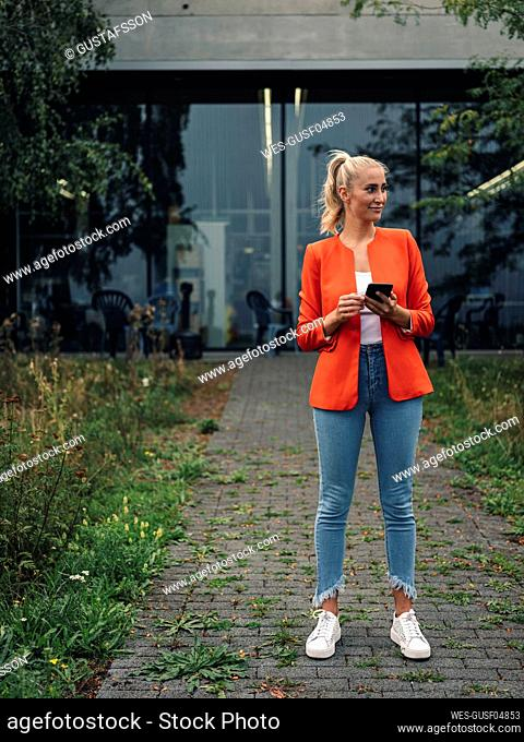 Young female entrepreneur with smart phone standing in company garden