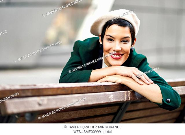 Portrait of smiling fashionable young woman sitting on a bench