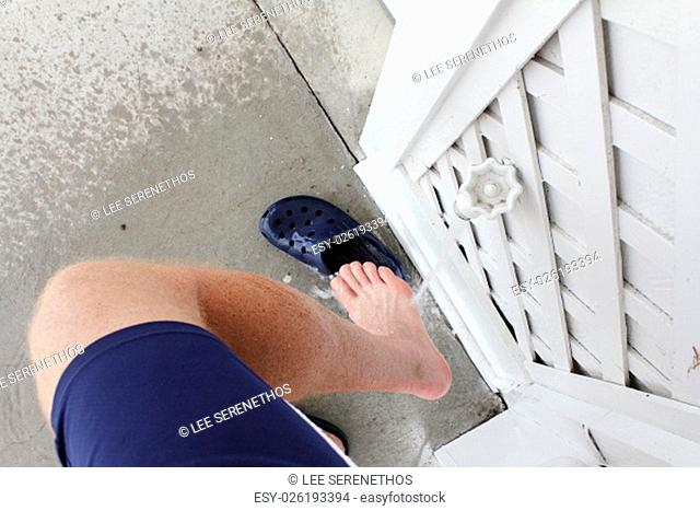Right leg of a mature male wearing blue sports shorts rinsing sand from his foot after visiting the beach. Outdoor water spigot spraying sand off a man's right...