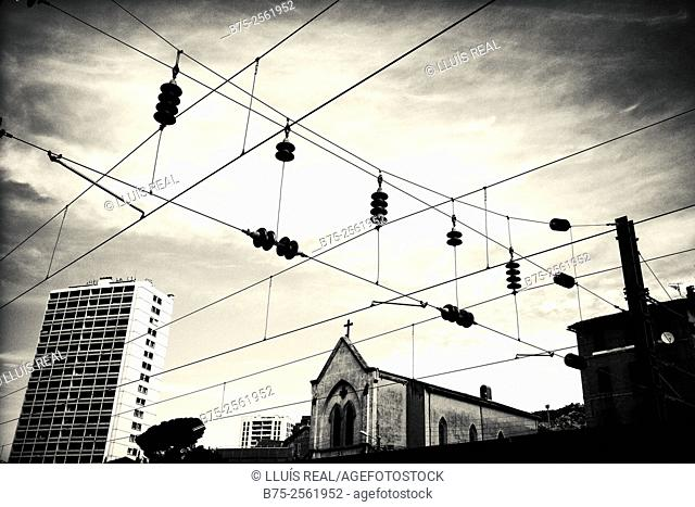 Forefront of the electrical wires of the railway station of Toulon, and in the background a residential building and a church