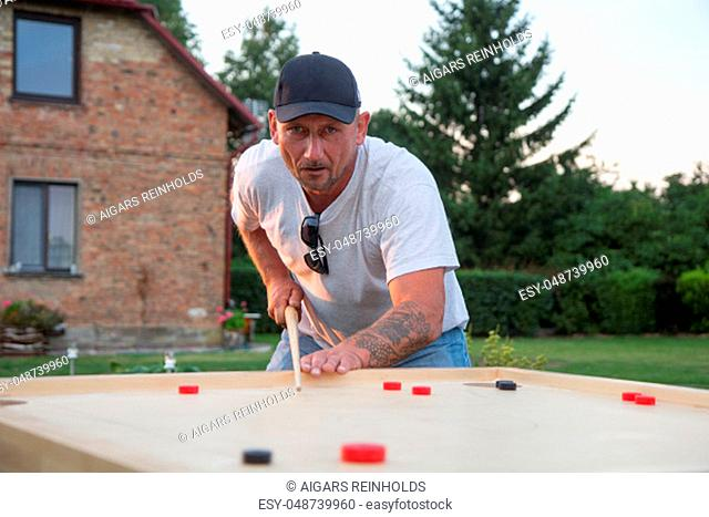 Man playing Novuss in outdoors. Novuss is a national sport in Latvia similar to pocket billiards or pool