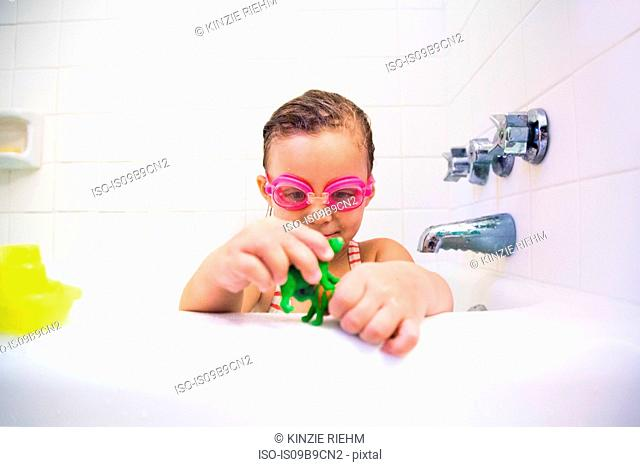 Girl wearing swimming goggles playing with toys in bath
