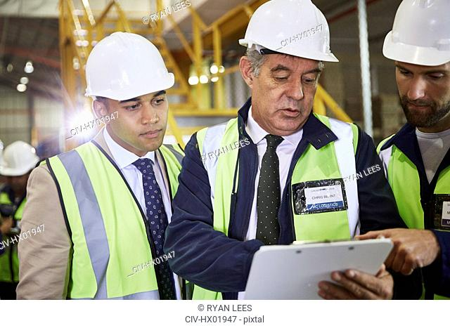 Managers with clipboard meeting in distribution warehouse