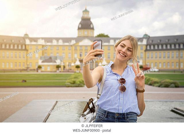 Germany, Karlsruhe, tourist taking selfie with smartphone