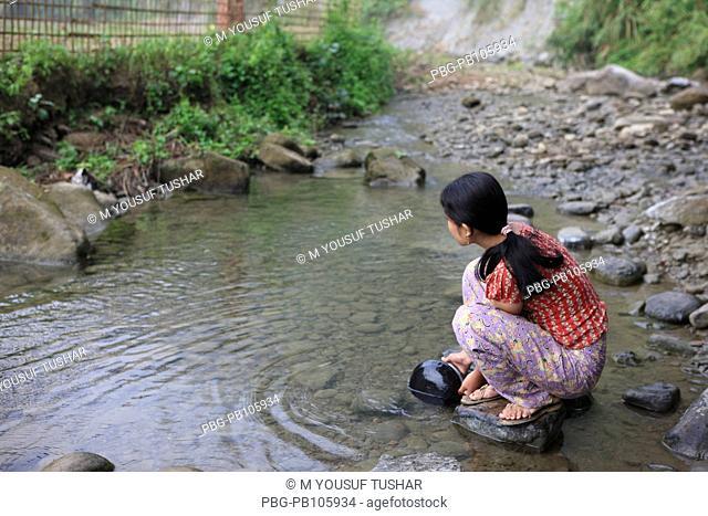 An ethnic girl washes utensils at the Sangu river at Thanchi Bandarban, Bangladesh December 2009